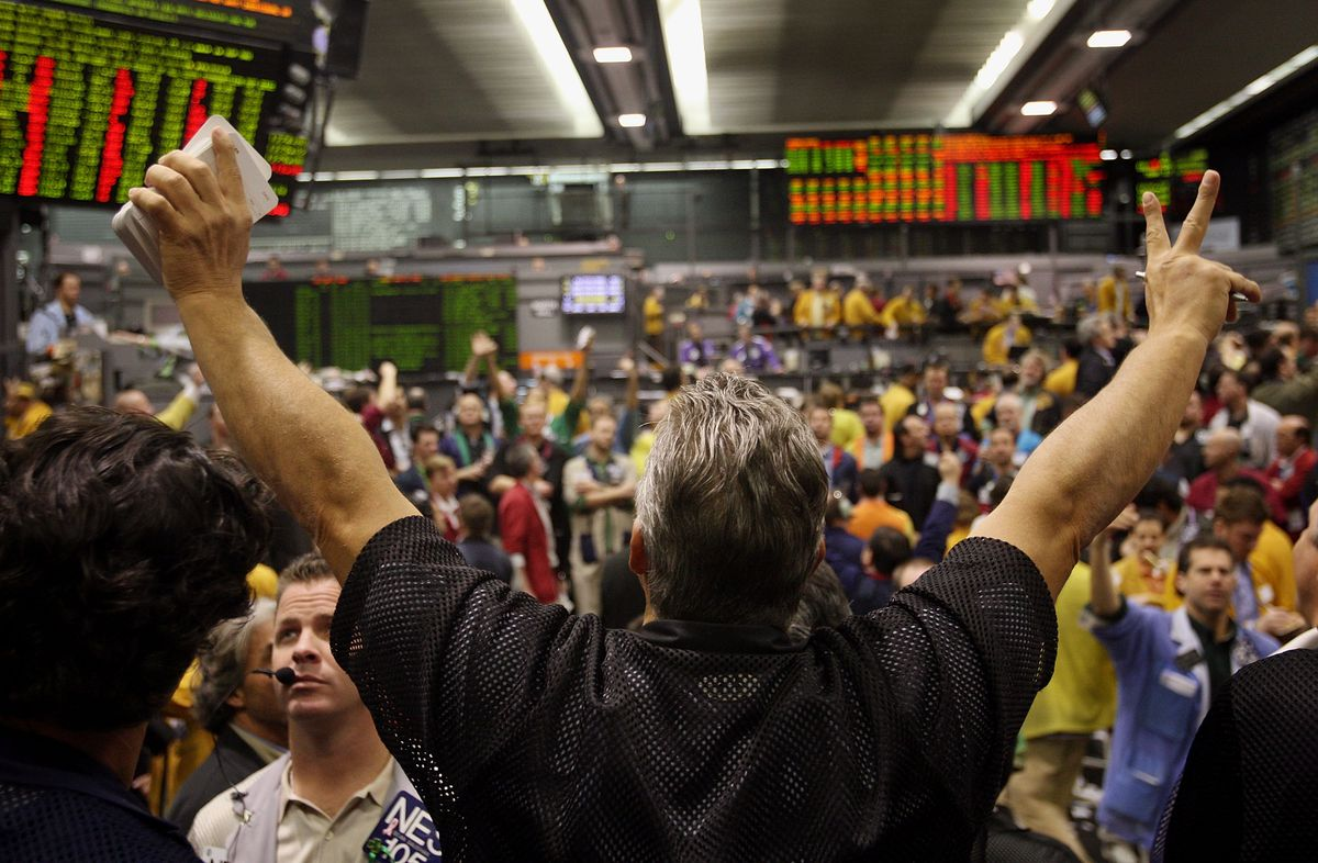 A trader holds his hands up in front of other traders on the floor.