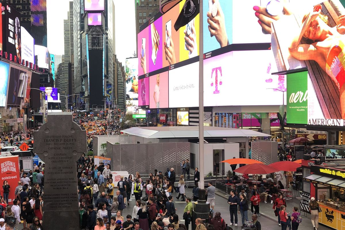 The pedestrian plaza in Times Square is full of people who are gathered around a solar powered prefab home. The billboards on the surrounding buildings are all brightly lit.