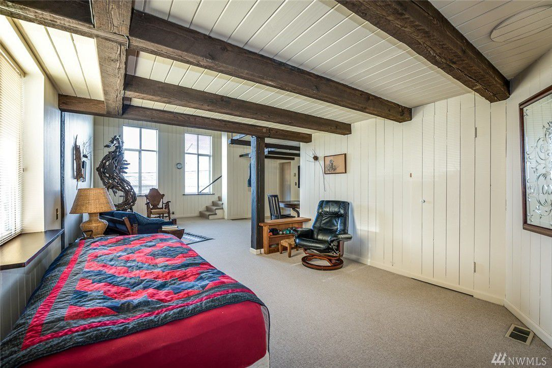 A bed underneath a loft with exposed beams