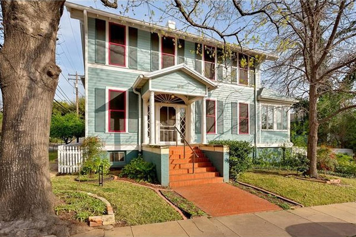Two-story wooden house with classical revival elements, light blue with red and white trim