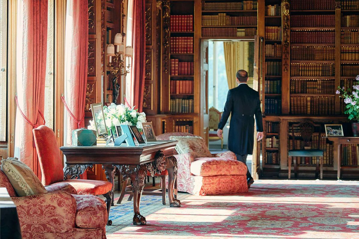A man walks in a library with a wall of books, and pink chairs and curtains.