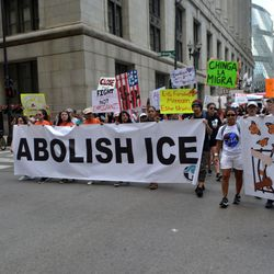 """Protesters carry a sign reading """"Abolish ICE"""" onSaturday while marching on Clark Street to protest anticipated raids by immigration authorities."""