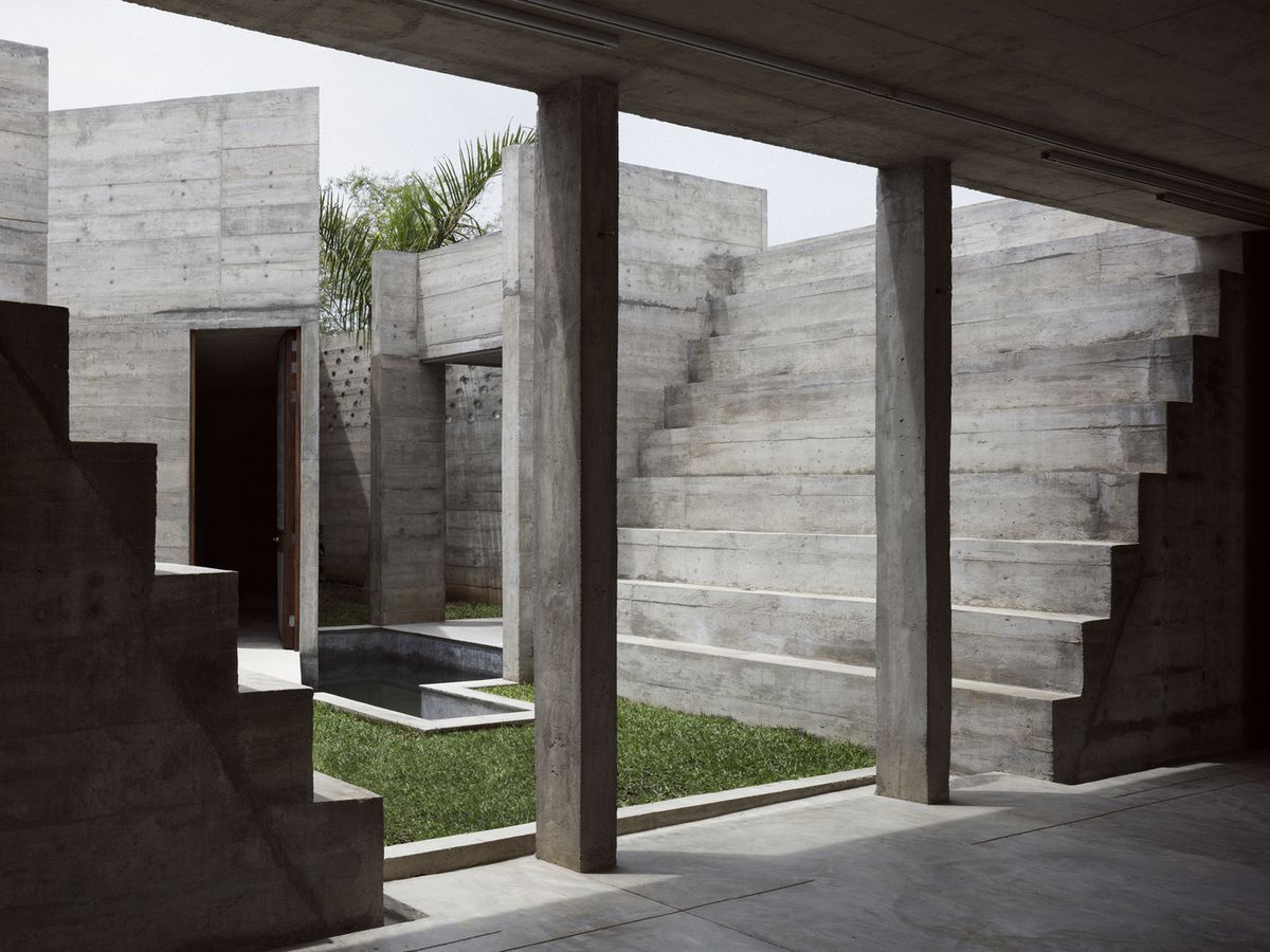 Pool and lawn inside concrete courtyard.