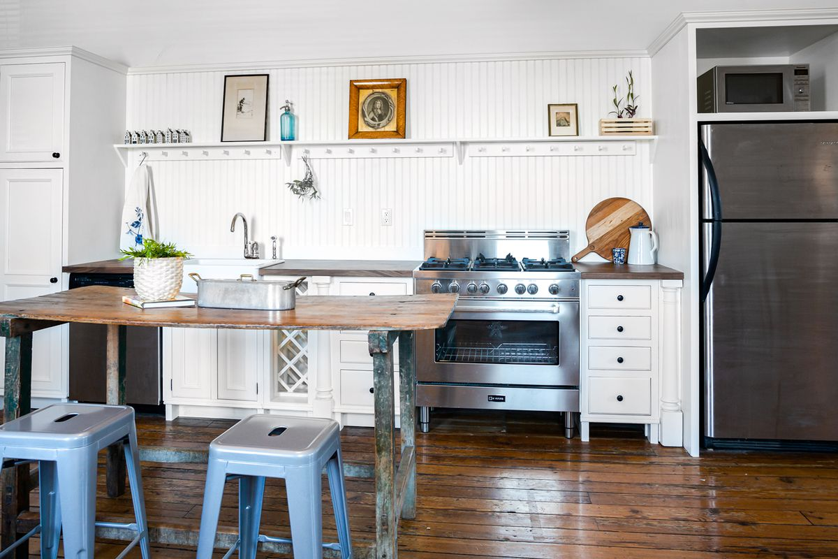 A kitchen with white cabinetry and wooden white panels.
