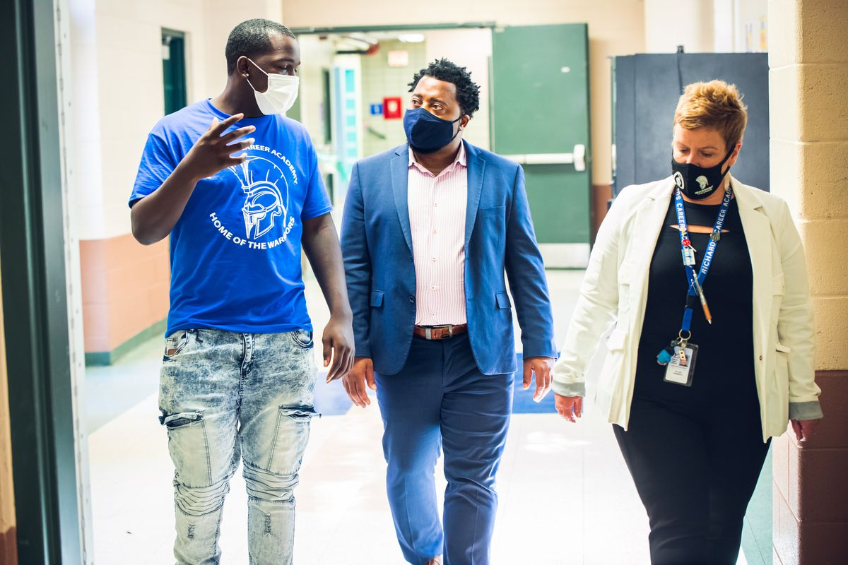 A young man in a T-shirt and jeans, an older man in a blue suit and a woman in a white jacket, all wearing face masks, are walking down a school hallway.