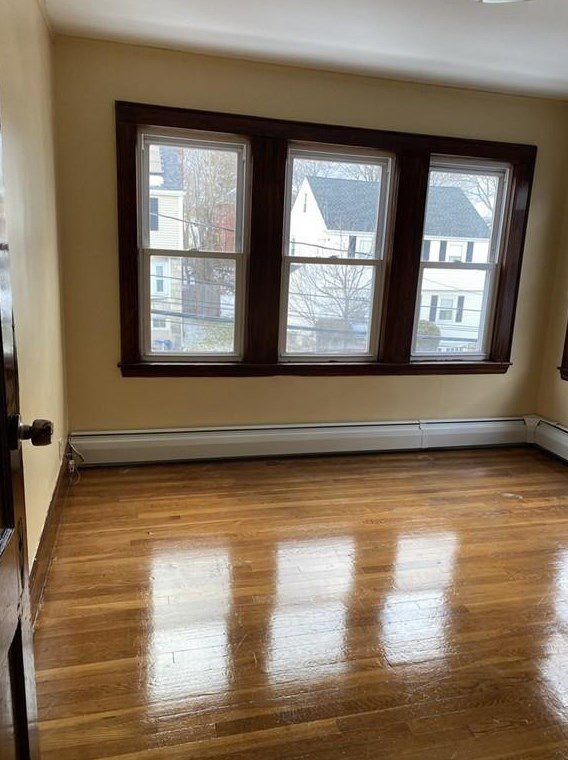 An empty bedroom with a set of three windows.