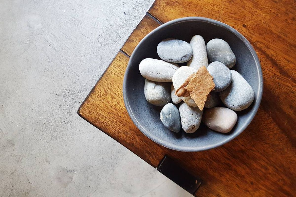A small bite from a tasting menu restaurant, served on a bowl of rocks.