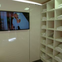 A flat screen shows an InStyle video about the Essentials shirts.