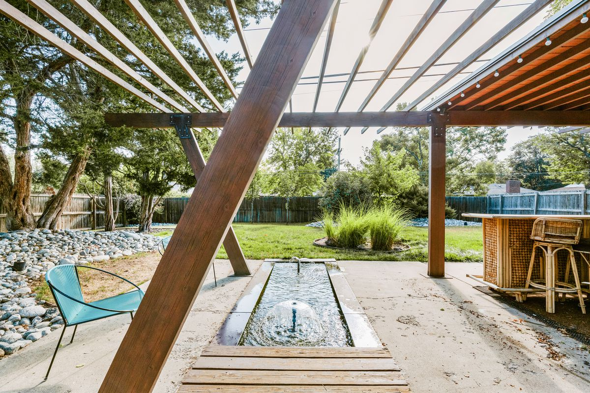A backyard area has a pergola and an in-ground water fountain on a patio.