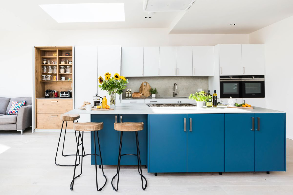 A bright kitchen with white cabinets on top and a blue kitchen island, Seats are arranged around the corner of one side of the island.