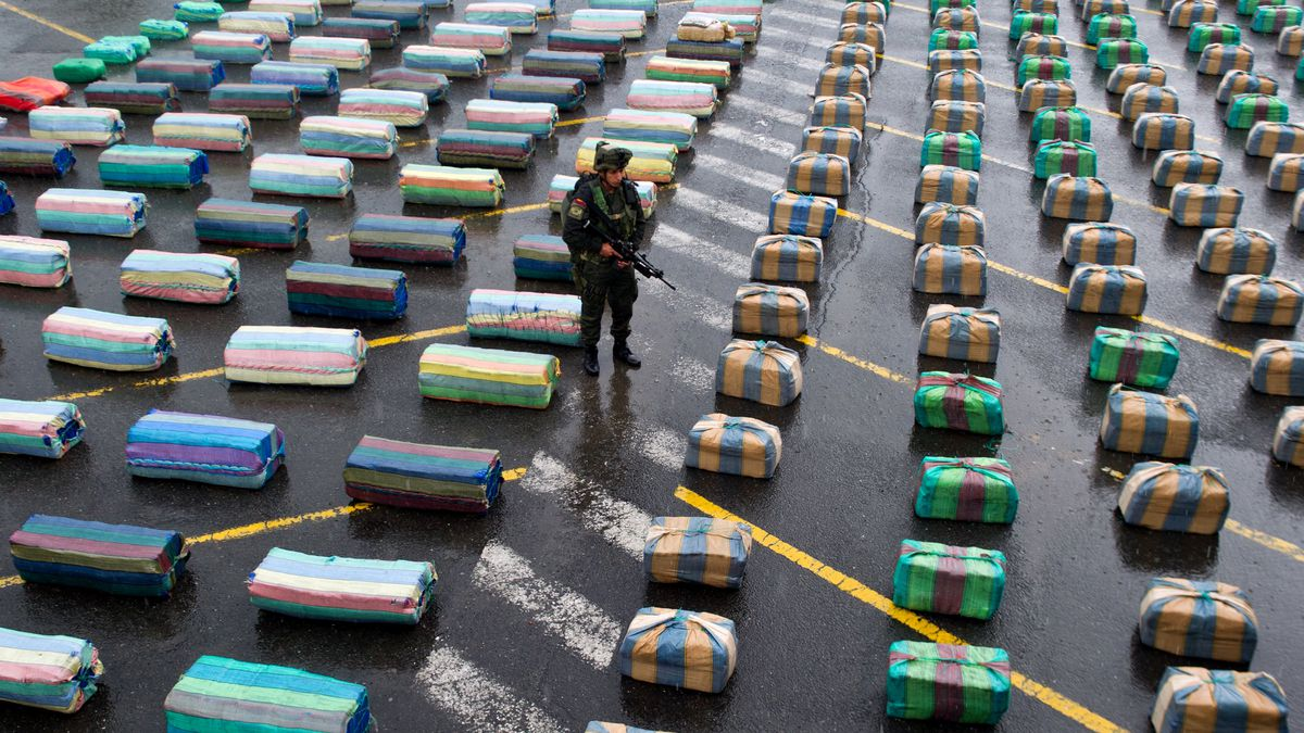 A soldier stands next to packages of marijuana in Colombia.