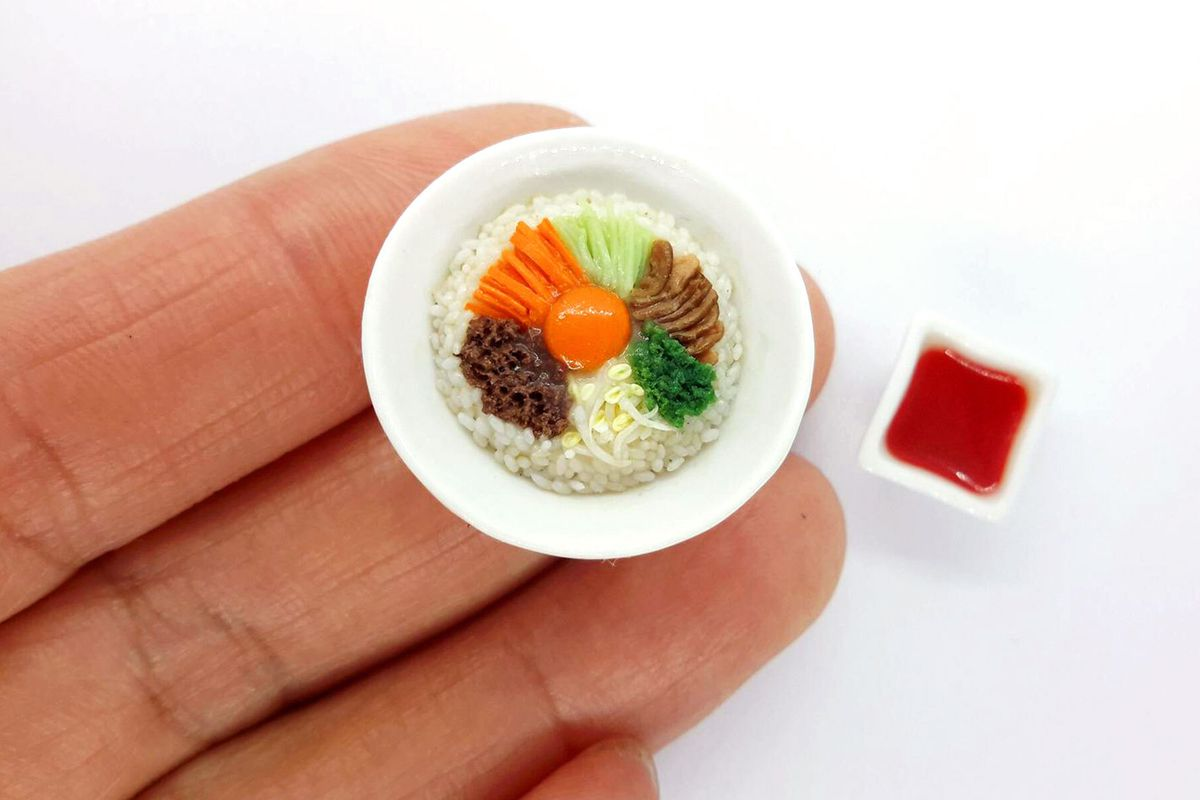 A miniature rice bowl on a hand for scale
