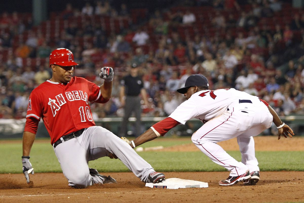 Aug 23, 2012; Boston, MA, USA; Los Angeles Angels left fielder Vernon Wells (left) is tagged out at third base by Boston Red Sox second baseman Pedro Ciriaco (right) during the tenth inning at Fenway Park.  Mandatory Credit: Mark L. Baer-US PRESSWIRE