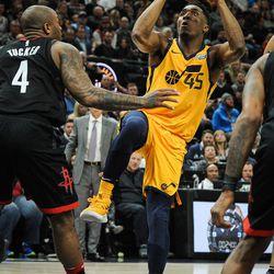 Utah Jazz guard Donovan Mitchell (45) goes up for a shot over Houston Rockets forward PJ Tucker (4) as the Utah Jazz host the Houston Rockets at Vivint Smart Home Arena Salt Lake on Thursday, Dec. 7, 2017.
