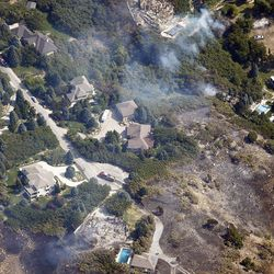 Two burned homes are seen at the mouth of Weber Canyon on Tuesday, Sept. 5, 2017, as a wildfire burns in the area.