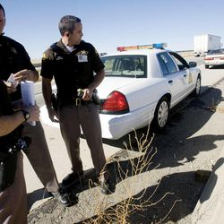 Utah Highway Patrol Troopers Kade Martinez, left, Ben Fallows and Mike Singleton discuss the results of a sobriety test Wednesday, Oct. 17, 2012, after administering it to a female driver on Bangerter Highway near 1300 South.