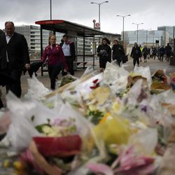 Pedestrians pass flowers on a memorial for victims at the London Bridge in London, Tuesday, June 6, 2017. British police on Tuesday named the third London Bridge attacker as an Italian national of Moroccan descent, and Italian officials said they had passed on their concerns about him to British intelligence officials last year.