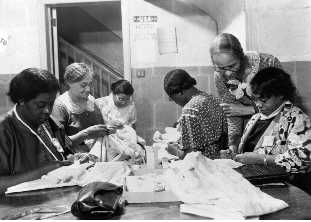 A group of older women sewing as part of a New Deal-era jobs program.