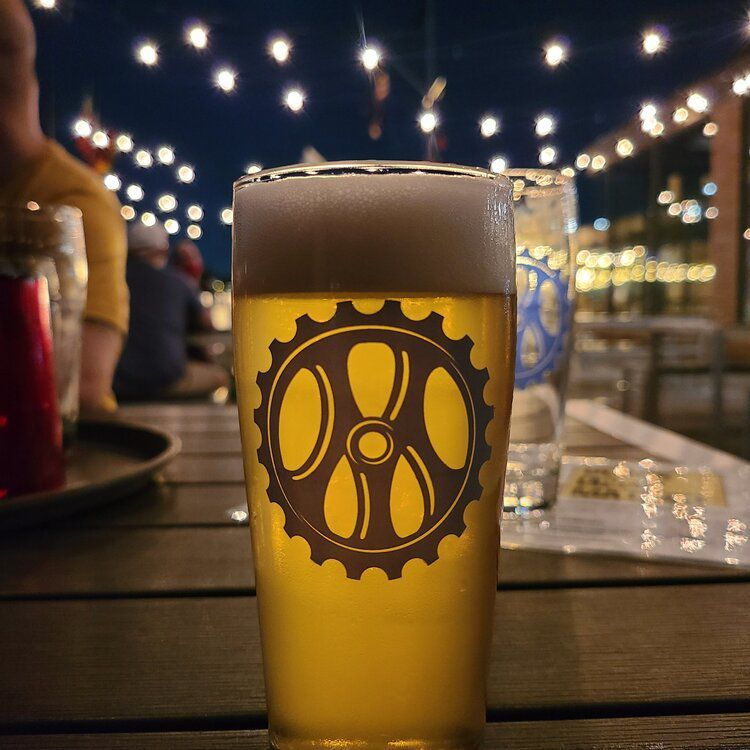 A glass of beer sitting on an outdoor patio table.