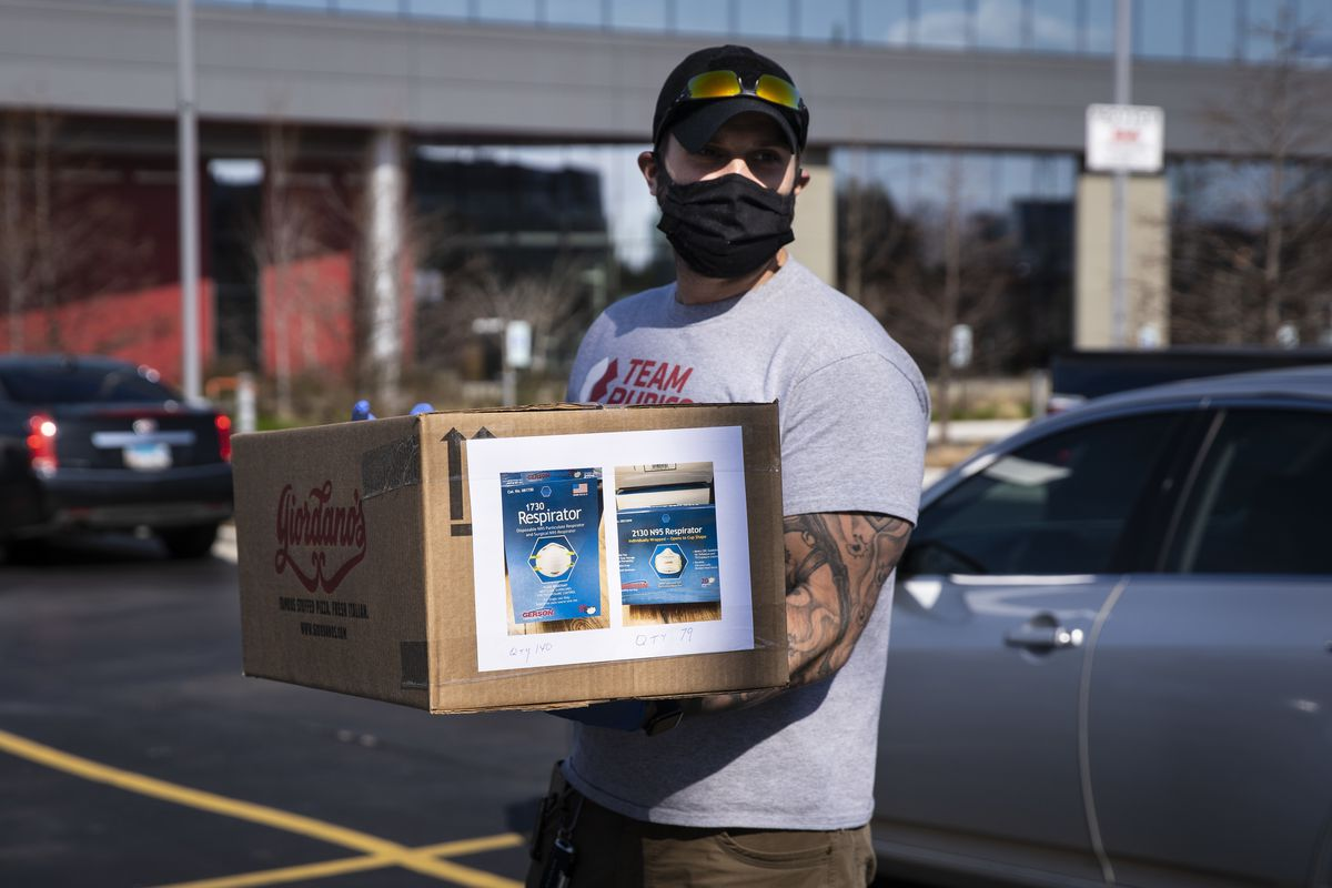 Kazimieras Urbonavicius wears a cloth face mask as he volunteers at a personal protective equipment drive at the United Center.