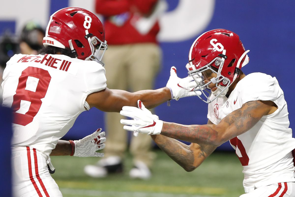 Wide receiver DeVonta Smith and wide receiver John Metchie III of the Alabama Crimson Tide celebrate a touchdown in the first half against the Florida Gators during the SEC Championship game at Mercedes-Benz Stadium on December 19, 2020 in Atlanta, Georgia.