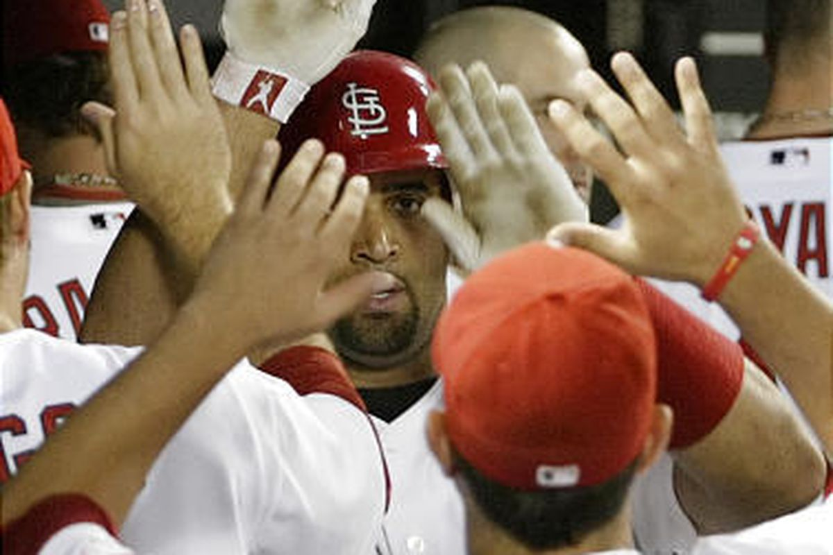 St. Louis Cardinals' Albert Pujols, center, celebrates with teammates after hitting a solo home run in the third inning.