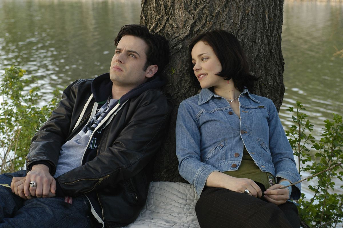 """Luke Kirby and Rachel McAdams, the stars of """"Slings & Arrows,"""" sit beside a river with their backs against a tree."""