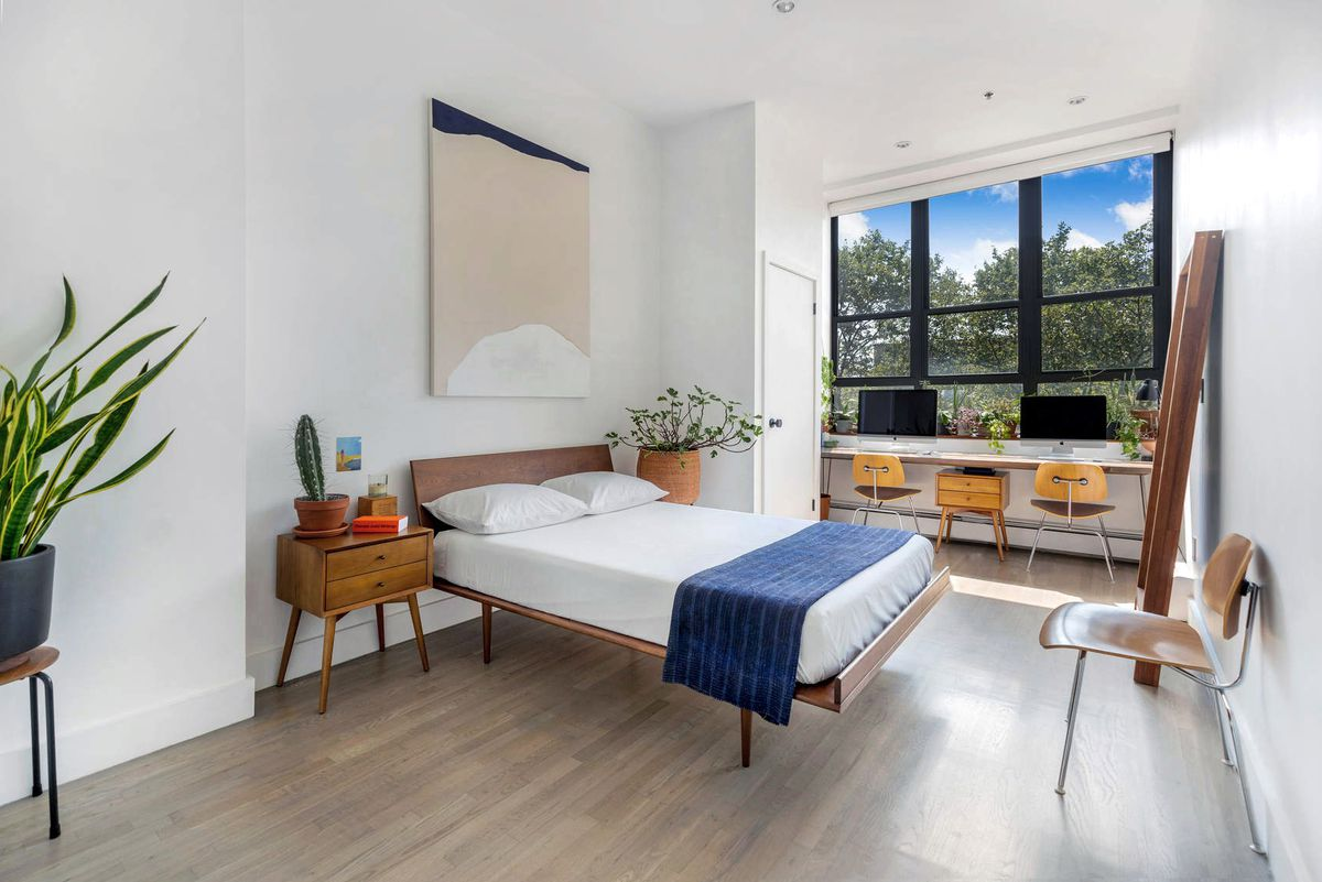 A bedroom with hardwood floors, a large casement window, a small bed, and several planters.