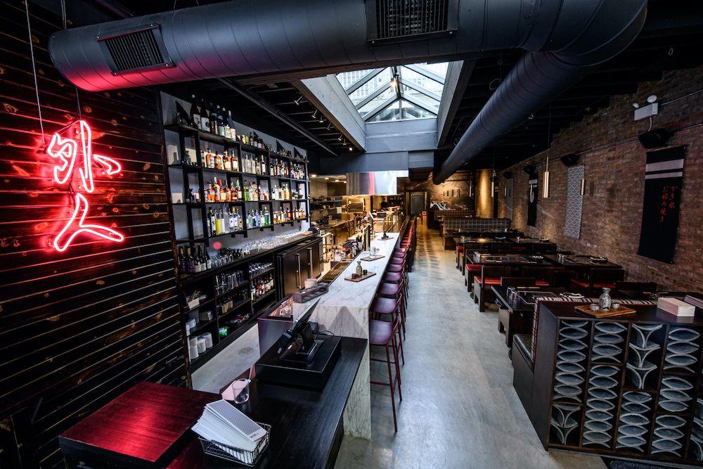 The inside of a dark-hued restaurant and bar.