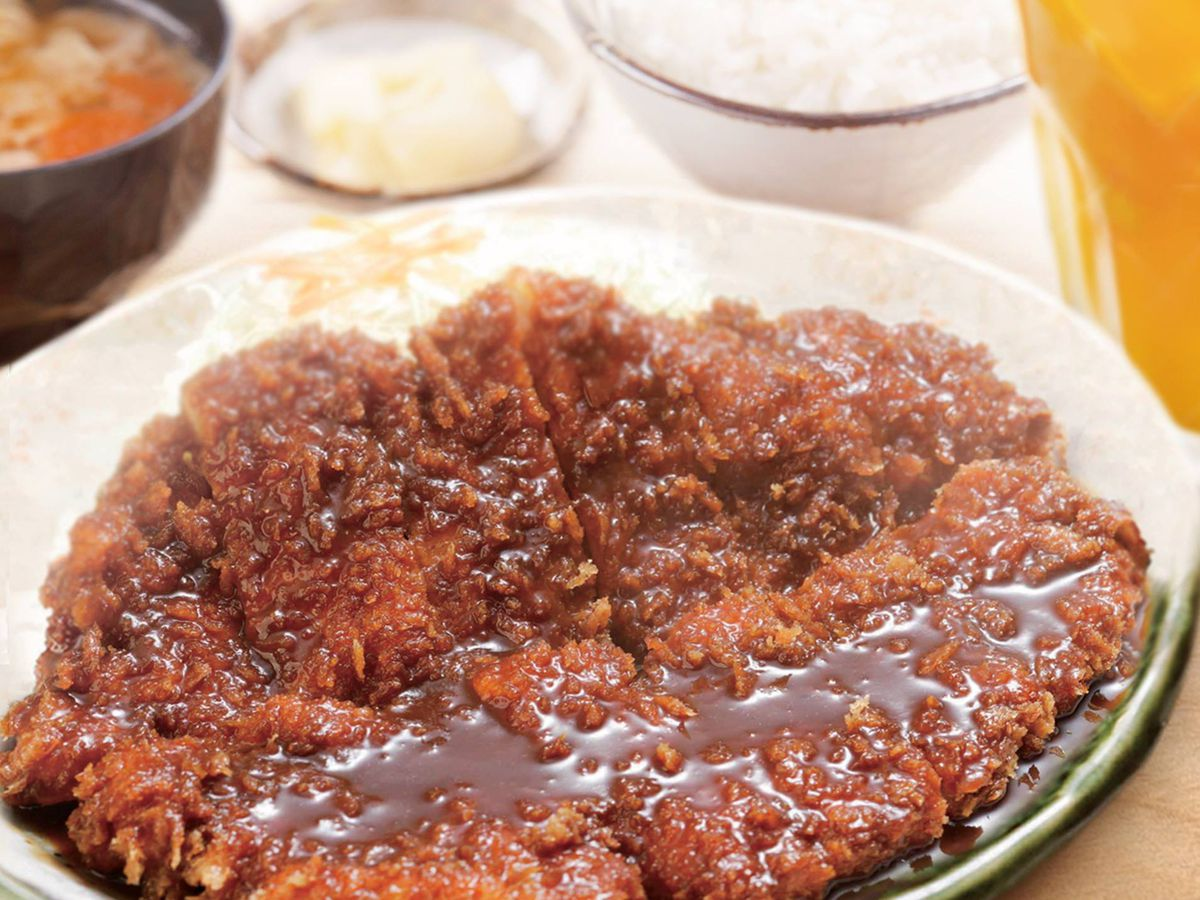 A large slab of deep fried pork topped with sauce sits upright on top of rice hidden behind with several other small dishes blurred in the background