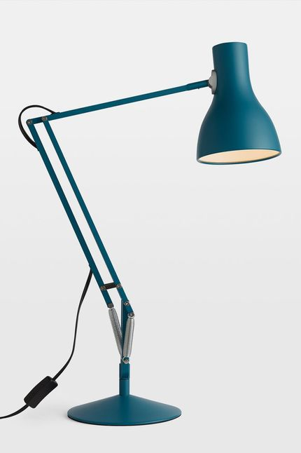 Blue lamp with flat round base and bent arms.