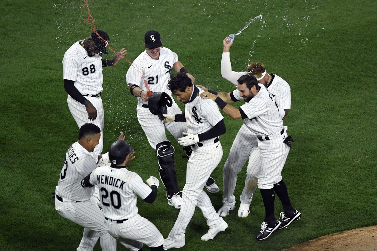 Nick Williams, center, is mobbed by White Sox teammates after his fielder's choice scored Nick Madrigal to defeat the Indians 4-3 in the bottom of the ninth inning Monday.