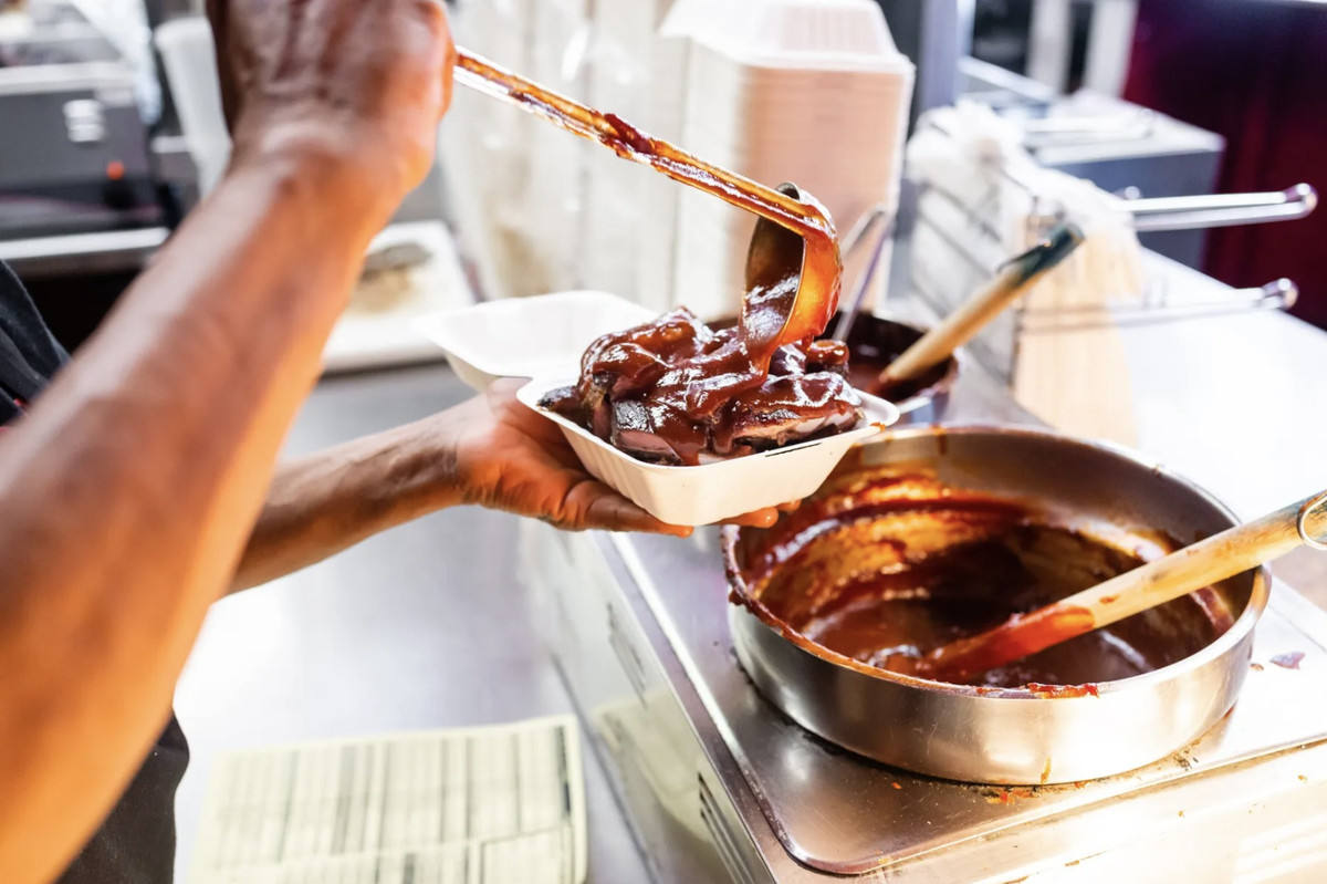 A restaurant worker pours barbecue sauce on top of meat.