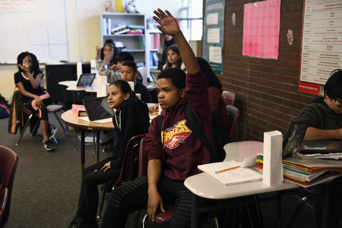 Russell Patton, hand raised high, waits to be called on during Ines Barcenas' sixth grade math class in March 2018 at East Middle School in Aurora.