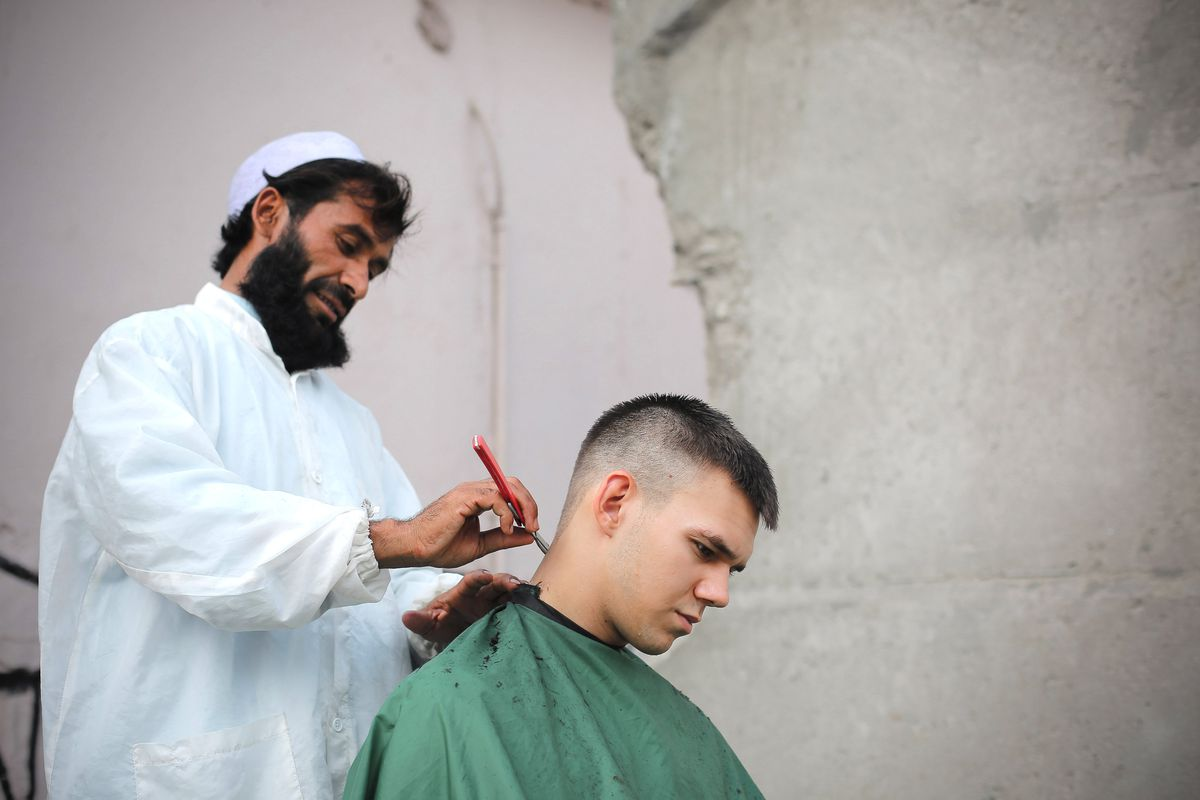 A barber cuts the hair of a US soldier at a base in Afghanistan