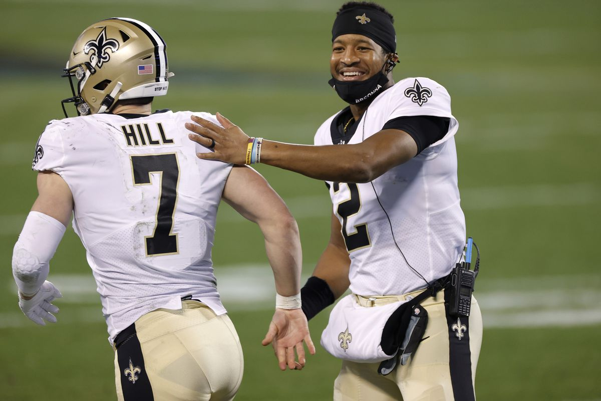 Quarterback Jameis Winston #2 of the New Orleans Saints shares a smile as he greets teammate quarterback Taysom Hill #7 during the second half of their game against the Carolina Panthers at Bank of America Stadium on January 03, 2021 in Charlotte, North Carolina.