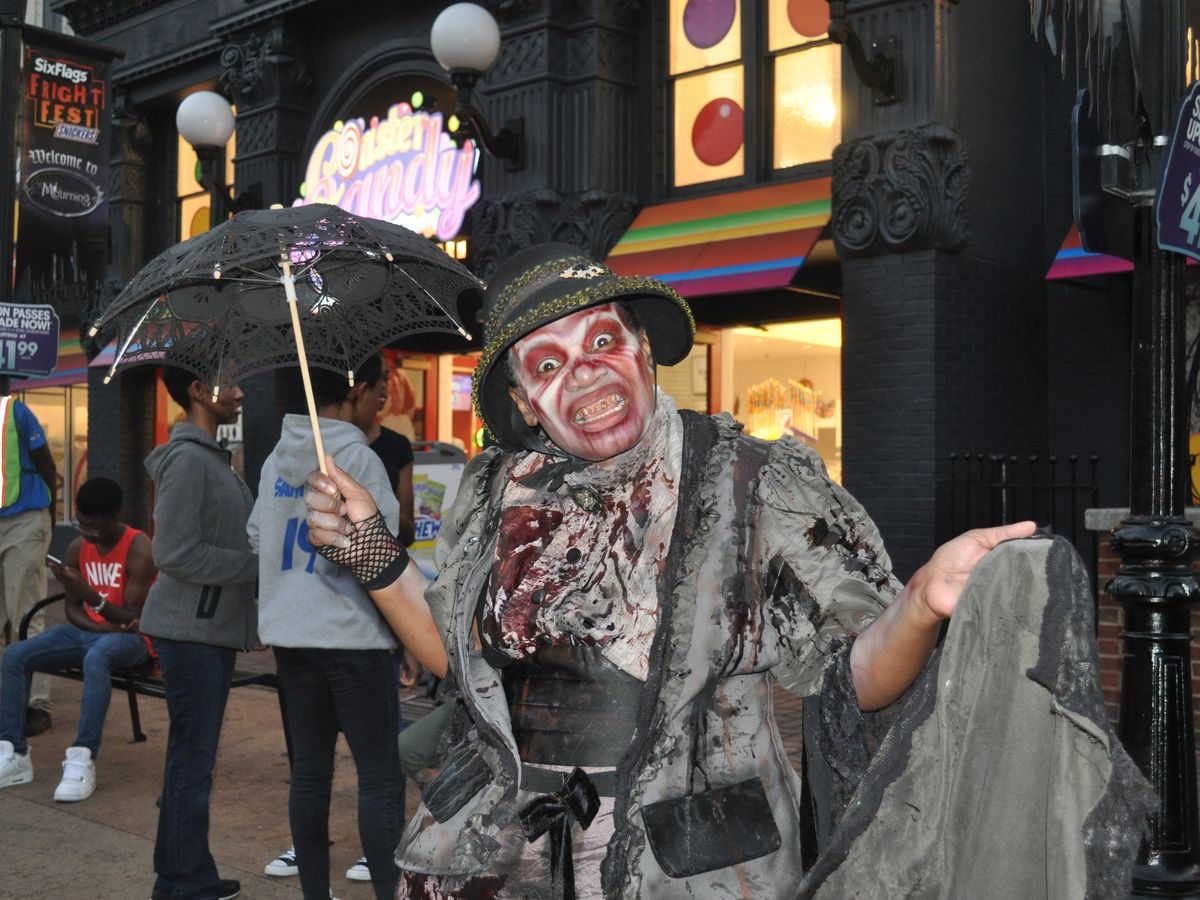 Zombie holding an umbrella with people and buildings behind her.