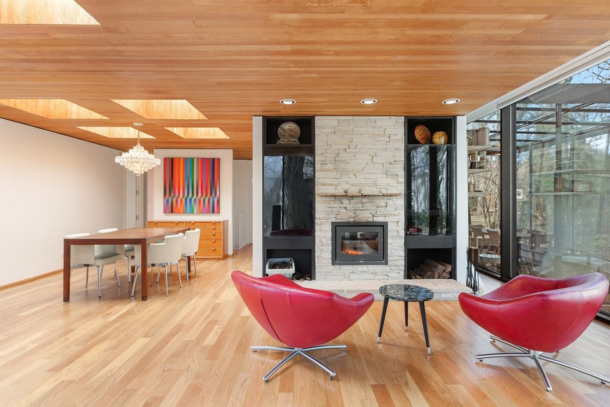 Two red chairs sit in front of a contemporary stone-lined fireplace in an open living and dining room with wood floors and ceilings.
