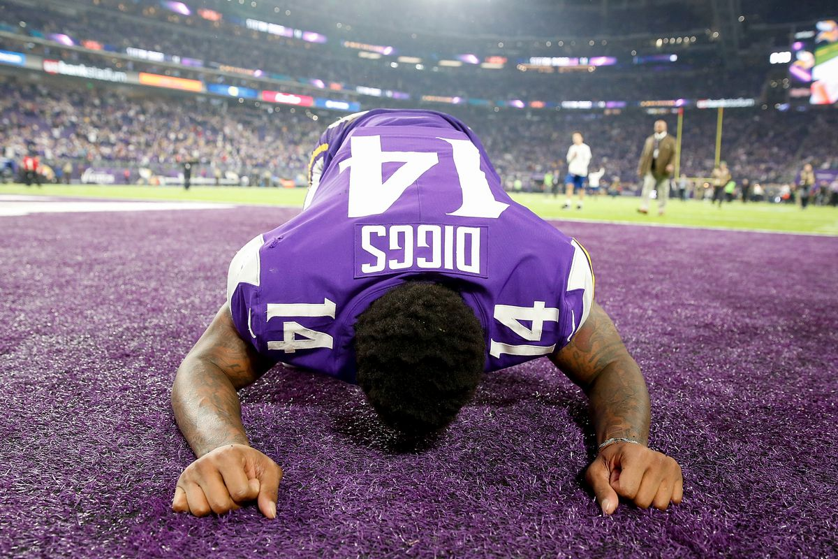 Stefon Diggs #14 of the Minnesota Vikings celebrates a win by kneeling and kissing the end-zone grass.
