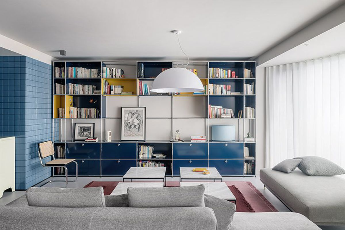 Inside a modern apartment living room, a wall of blue shelving holds books and artworks. Light gray sofa and lounge surround a set of four white marble top coffee tables.