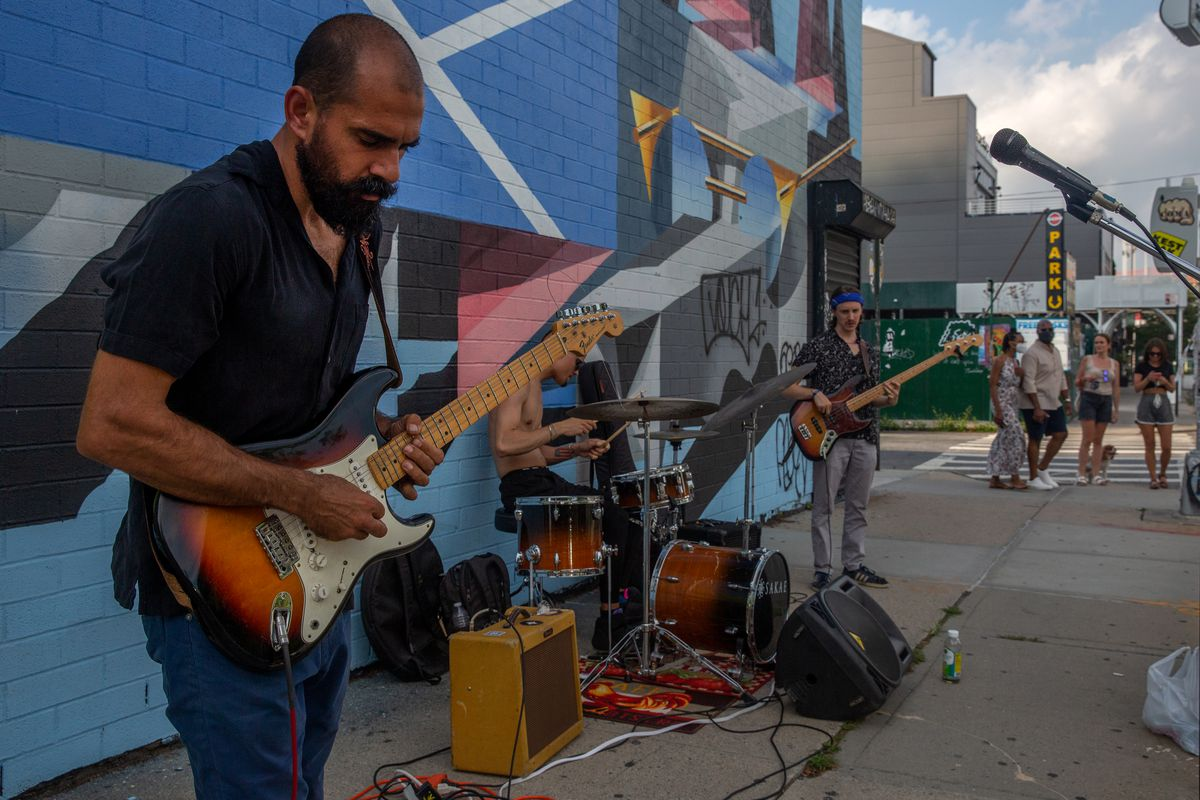 A blues band entertains people enjoying an open street in Williamsburg during the coronavirus outbreak, July 17, 2020.