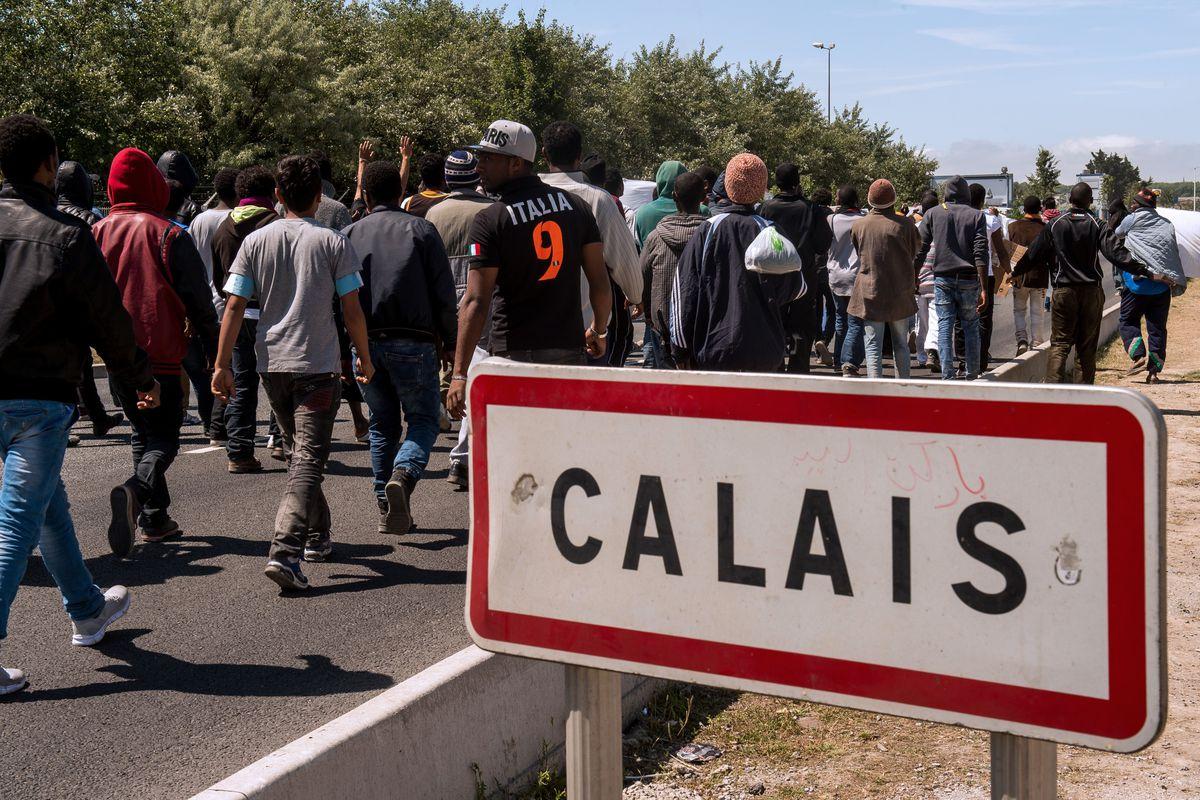 Migrants walk toward the ferry port of Calais in June 2015.