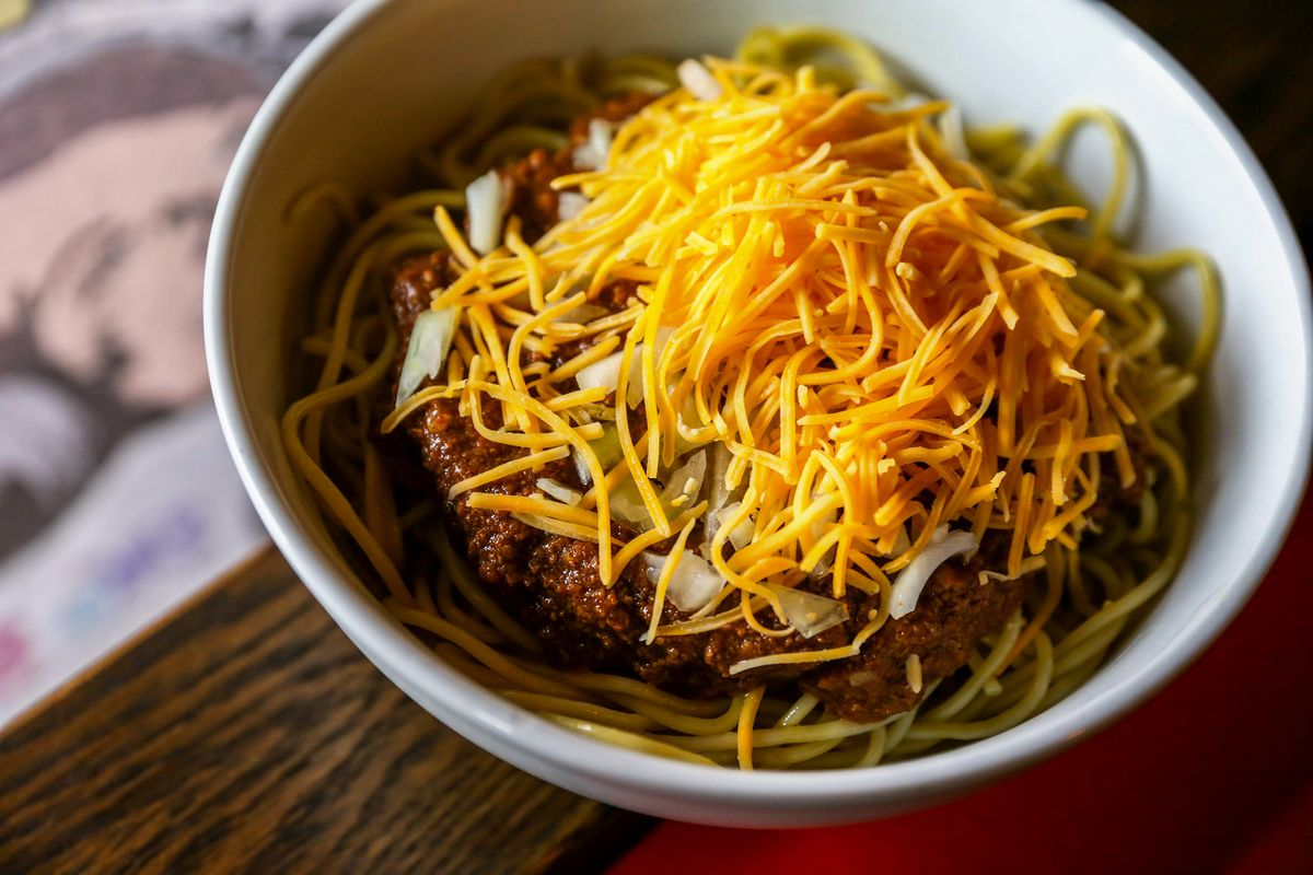 A bowl of noodles with chili, onions, and cheese at Cascade Chili Co.
