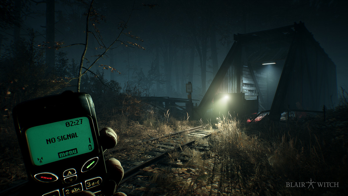 Blair Witch - The player holds an old school cell phone, which reads NO SIGNAL. He stands in the woods at night, looking at an ominously lit structure.