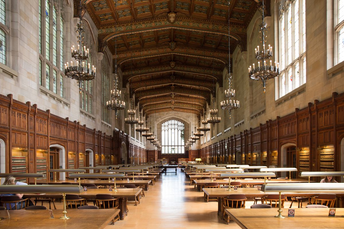 The interior of the William W. Cook Legal Library in Michigan. There are rows of tables with chairs on the floor. The ceiling is vaulted with an ornamental design. There are hanging chandeliers.