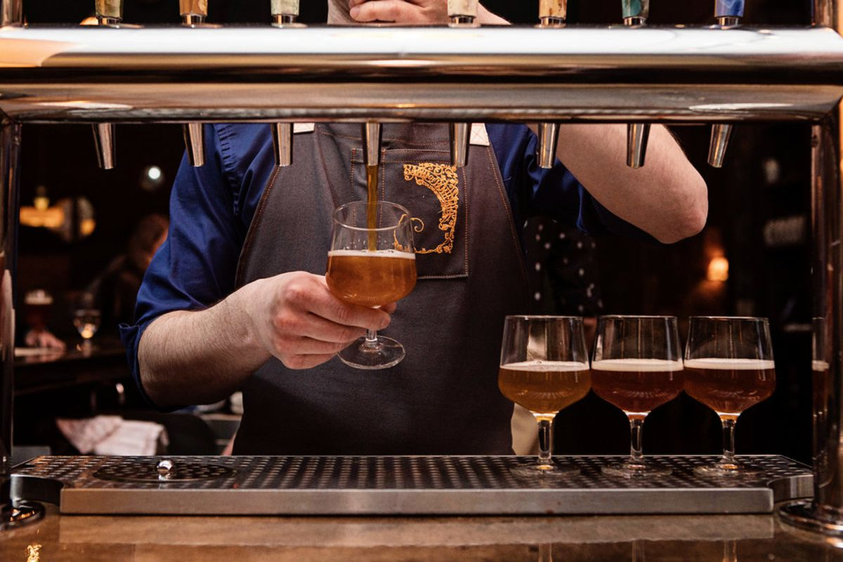 A bartender in a blue shirt and brown apron pours beer from a tap into a tulip-shaped glass.