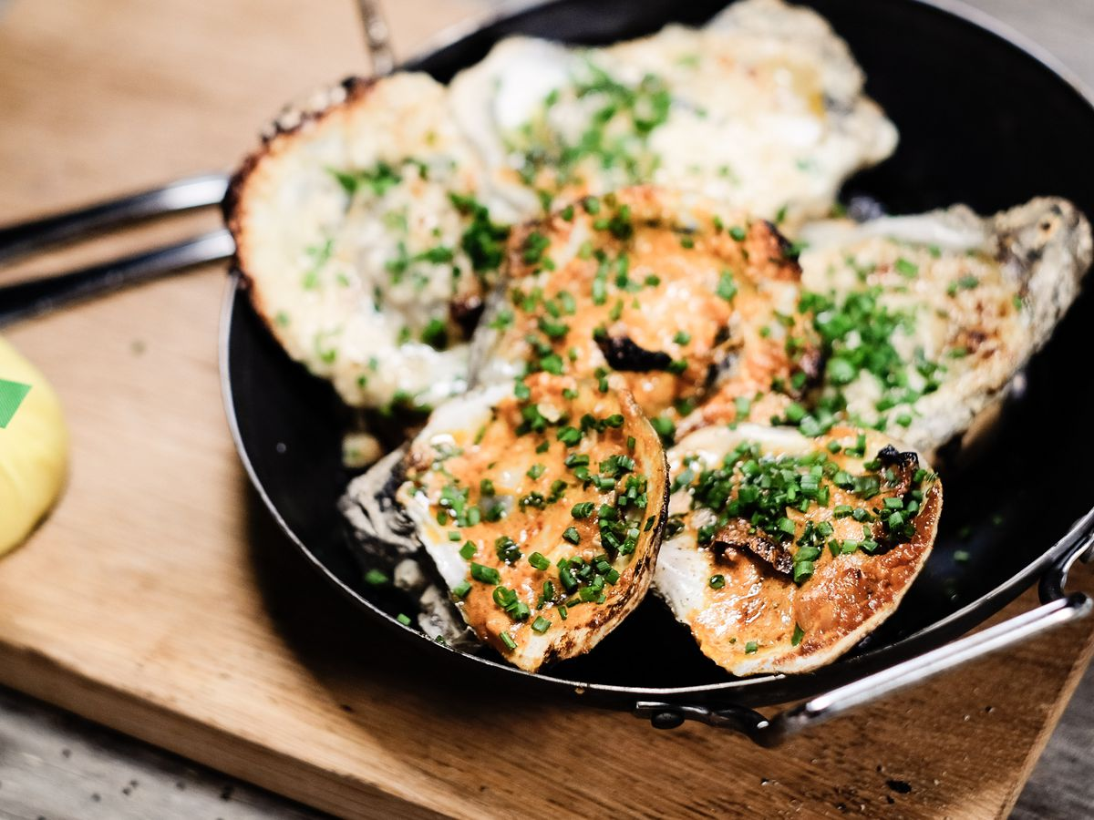 Grilled oysters topped with chives and served in a skillet