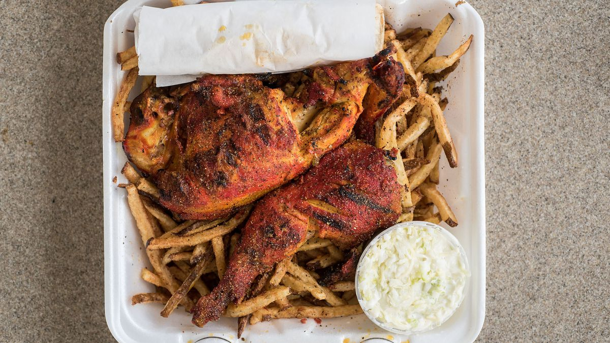 A Styrofoam tray of grilled chicken with fries beneath.
