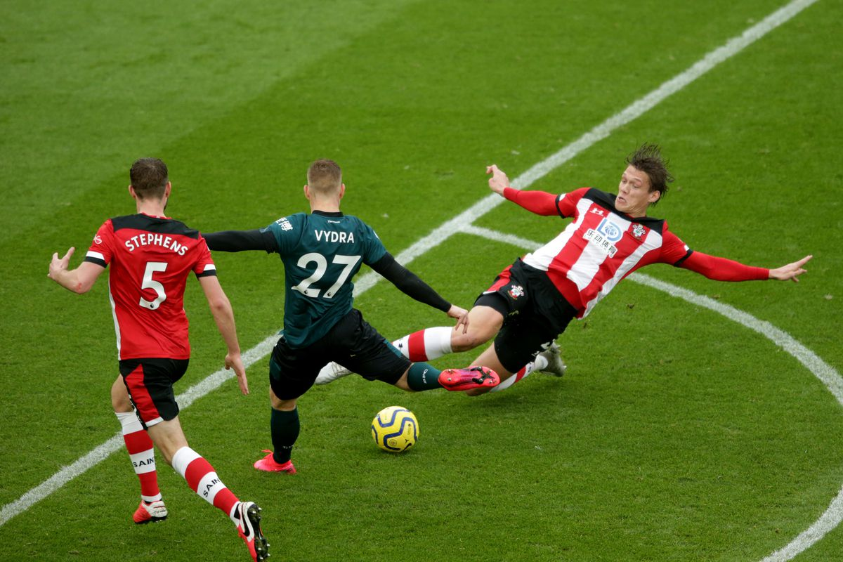 Southampton FC defenders Jack Stephens and Yannik Vestergaard challenging for the ball against Burnley in the Premier League before coronavirus covid-19 pandemic took hold in the UK