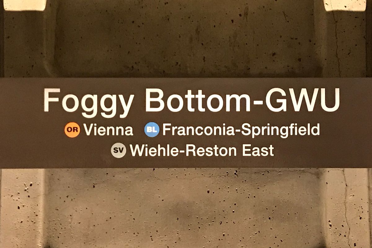 A Metro station sign along the wall of a subway station.